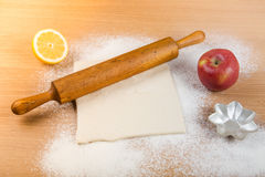 Dough, rolling pin, forms for baking, apple, half of lemon and f Stock Images