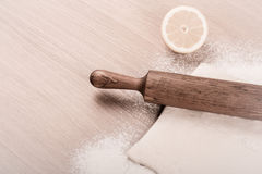 Dough, rolling pin, half of lemon and flour sprinkled on a light Royalty Free Stock Photos