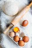 Dough, rolling pin and a tray of eggs. Royalty Free Stock Photos