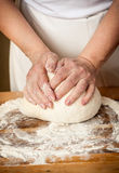Dough_17. Woman's hands knead the dough Royalty Free Stock Photography