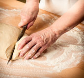 Dough_10. Woman's hands slice the dough Royalty Free Stock Photo