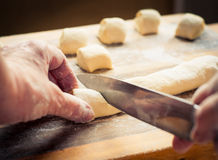 Dough_5. Woman's hands slice the dough Stock Images