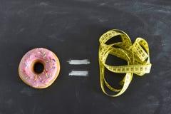 Doughnut και ο ράφτης μετρούν την ταινία στον πίνακα στη γλυκιά κατάχρηση ζάχαρης και το ίσο υπερβολικό βάρος σωμάτων εθισμού Στοκ Φωτογραφίες