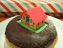Doughnut λούστρου σοκολάτας που ολοκληρώνεται με τη διακόσμηση εξοχικών σπιτιών ζάχαρης για τα Χριστούγεννα Στοκ εικόνα με δικαίωμα ελεύθερης χρήσης
