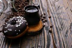 Doughnut με τη μαύρη τήξη και η σοκολάτα κονιοποιούν και ένα αυθεντικό φλυτζάνι του ισχυρού καφέ Το Α μπορεί των φασολιών καφέ κα στοκ εικόνα