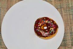 Doughnut σοκολάτας σε ένα άσπρο πιάτο Στοκ εικόνα με δικαίωμα ελεύθερης χρήσης