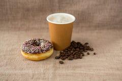 Doughnut, φασόλια καφέ και καφές στο υπόβαθρο λιναριού στοκ εικόνες
