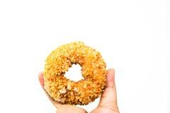 Doughnut φυστικιών εκμετάλλευσης χεριών ατόμων απομονώνει Στοκ φωτογραφία με δικαίωμα ελεύθερης χρήσης