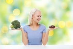Χαμογελώντας γυναίκα με το μπρόκολο και doughnut Στοκ φωτογραφία με δικαίωμα ελεύθερης χρήσης