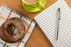 Doughnut coffee and notepad with pen Stock Images