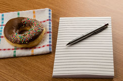 Doughnut coffee and notepad with pen Royalty Free Stock Images