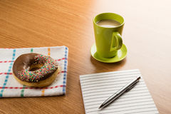 Doughnut coffee and notepad with pen Royalty Free Stock Photo