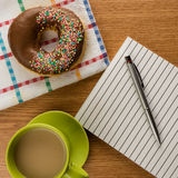 Doughnut coffee and notepad with pen Stock Photo