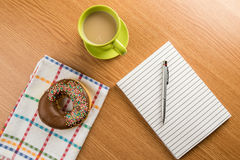 Doughnut coffee and notepad with pen Royalty Free Stock Photos