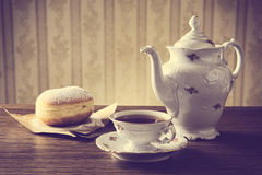 Doughnut with cup of tea on table in old-fashioned Royalty Free Stock Photography
