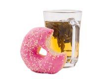 Doughnut die met een kop thee op een wit geïsoleerde achtergrond wordt gebeten royalty-vrije stock fotografie