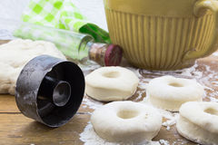Doughnut dough on floured oak wood table with vintage cutter and Royalty Free Stock Photo