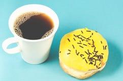 doughnut en coffe kop op blauwe achtergrond/Doughnut die in geel wordt geïsoleerd royalty-vrije stock foto's