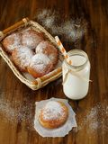 Doughnut and a glass jar of milk. On a wooden table royalty free stock images