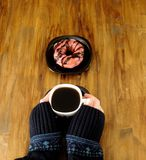Doughnut with glazing and a cup of coffee in woman`s hands. Doughnut with pink glazing and a cup of hot coffee in woman`s hands on a wooden table Royalty Free Stock Photos
