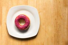 Doughnut met blueburry bovenste laagje in witte plaat op houten achtergrond Stock Foto