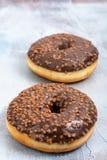 Doughnut met Chocoladebovenste laagje wordt gevuld op de Blauwe Achtergrond die royalty-vrije stock afbeeldingen