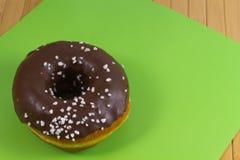 Doughnut met chocoladesuikerglazuur op groene achtergrond royalty-vrije stock afbeelding