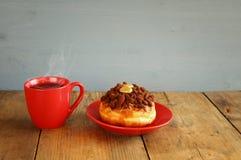 doughnut naast kop van koffie op houten oude lijst Stock Foto's