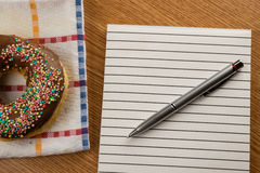 Doughnut and notepad with pen Stock Photos