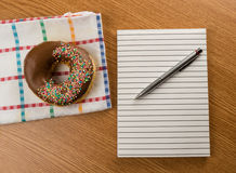 Doughnut and notepad with pen Stock Image