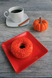 Doughnut orange with spice pumpkin coffee Royalty Free Stock Images