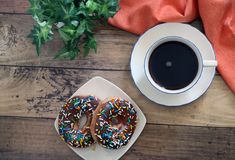 Doughnut with sprinkles and Coffee. Flat lay doughnut with sprinkles on Rustic Wood Stock Image