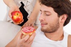 Doughnut tegenover appel Stock Afbeeldingen
