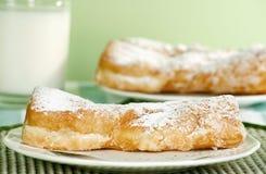 Doughnut twists. Two fresh baked doughnut twists on a green tablecloth Stock Photos