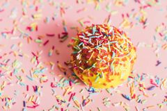 Sprinkled yellow doughnut on pink background. Doughnut with yellow icing and colorful sprinkles on a sprinkled pink background Stock Image