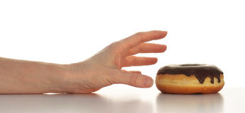 Doughnut Yummmm. Arm with hand reaching for a yummy chocolate topped doughnut (top half of photo isolated on white Royalty Free Stock Photography