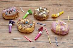 Doughnuts που επιδεικνύονται με τα κεριά γενεθλίων και τους ανεμιστήρες κομμάτων Στοκ εικόνες με δικαίωμα ελεύθερης χρήσης