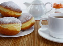 Doughnuts. Doughnuts and cup of tea on a table stock photo