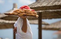 Doughnuts for all. Man selling doughnut on the beach. Neoi Poroi, Greece stock images