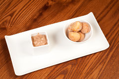 Doughnuts and chocolate mousse. Spiced doughnuts and chocolate mousse in bowls on a white platter Stock Images
