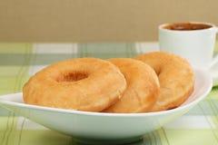 Doughnuts and coffee. Three sugar glazed ring doughnuts and coffee Royalty Free Stock Images