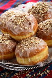 Doughnuts with frosting. Dusted nuts on the plate Stock Photo