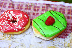 Doughnuts with green mint and pink strawberry frosting Stock Photos