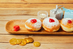 Doughnuts with jam on wooden plate with golden coins for Jewish Holiday Hanukkah. Doughnuts with jam on wooden plate for Jewish Holiday Hanukkah over wood table royalty free stock photography