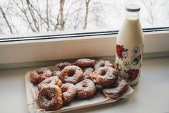 Doughnuts and Milk Bottle Near Clear Glass Window Stock Photography