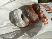 Doughnuts in powdered sugar on white paper stock image