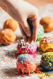 Doughnuts sprinkled by a woman with sugar sprinkles. Little doughnuts sprinkled by a woman with colorful sugar sprinkles. Decorating process Royalty Free Stock Image