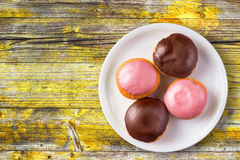 Doughnuts with sweet topping on a plate, top view Stock Photography