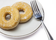 Doughnuts. View of a plate with two cakes and a fork at the side Royalty Free Stock Photography