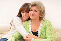 Doughter umarmt Mutter Stockbild